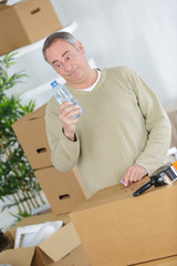 tired man with cardboard boxes drinking water