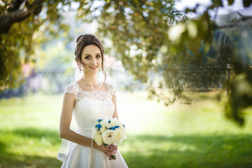 The bride  at a high cliff near the river. Walk the newlyweds. Wedding day. The best day of a young woman