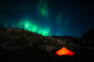 a tent in the night under northern lights