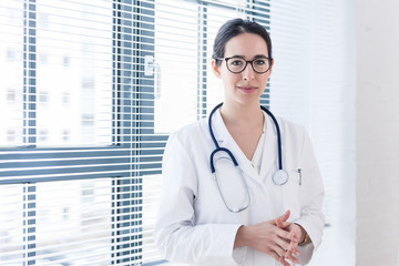 Portrait of a young nurse or physician wearing eyeglasses and white medical gown while looking at camera with confidence and serenity indoors