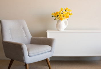 Retro style armchair with white cabinet and daffodils in white jug