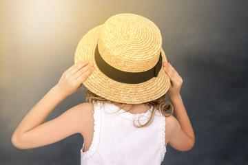 girl holding hands a straw hat.