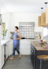 Woman walking through newly designed kitchen with wood island