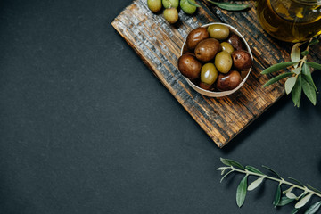 Dark and green olives, oil and leaves on a wooden board, top view, space for text