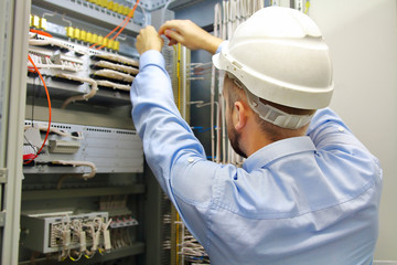Electrician engineer at work inspecting cabling connection in industrial automation control fuseboard.