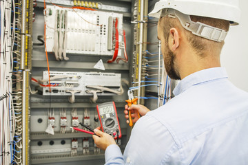 Electrical engineer adjusts control cabinet with multimeter and wire cutters. Testing of electrical automation cabinet by professional