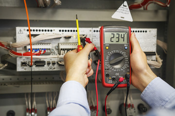multimeter and screwdriver in hands of electrical engineer for automation close-up. Adjustment of industrial control controller. Testing of electrical equipment.