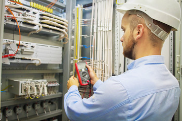 Engineer electric with multimeter. Side view of male technician examining fusebox with multimeter probe.