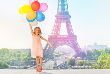 Happy little girl flying with colorful balloons