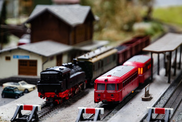 A train model diorama with a steam and an electric locomotive