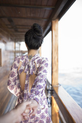 Girl holding hands with her lover walk forward on the yacht in s