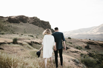 young fashionable couple walking through desert landscape