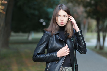 Art portrait of a young pretty brunette woman posing outdoors in black leather coat againt city park blurry background