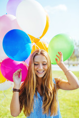 Portrait of a blonde girl having fun with colorful balloons.
