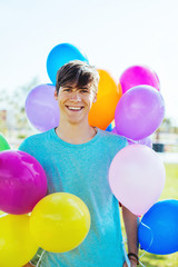 Portrait of a young boy smiling between colorful balloons.