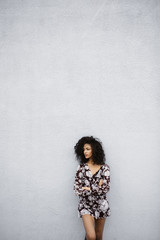 Pretty Young Woman Standing Against Blank Wall