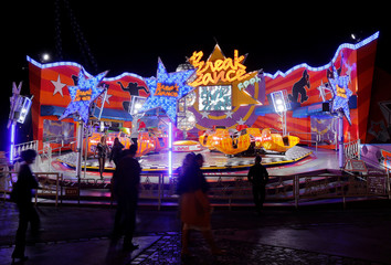 People walk by an attraction at Prater amusement park in Vienna