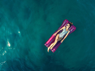 Overhead view of a woman relaxing on inflatable in sea