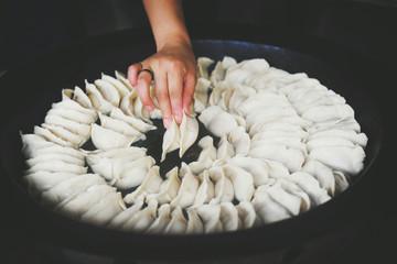 Woman placing dumplings in a pan in Shanghai China