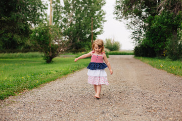 Toddler girl walking barefooted down a gravel driveway.