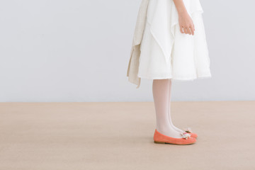 Young female with white dress and orange shoes