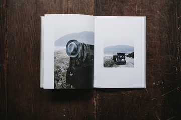 open book with photos of traveler's car at coast