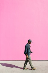 A young man with a camera walking by a hot pink wall.
