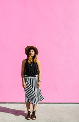 A young woman standing by a hot pink wall.