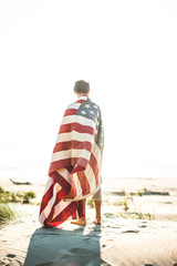 A young man covered in American flag enjoying beach
