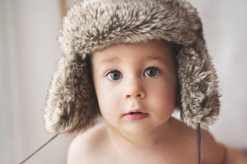 Portrait of a cute young boy wearing a furry winter hat