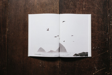 book of coast inspired photographs open on wood table
