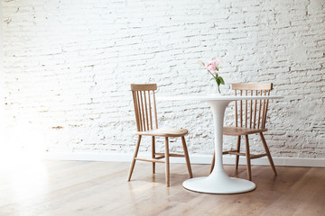 Simple room interior with table and chairs against of white painted room