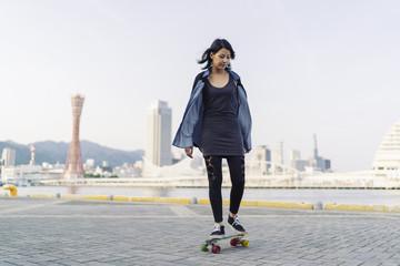 attractive young asian woman skating in Kobe Japan