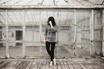 young woman standing on wood platform outside abandoned building