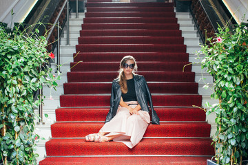 Young Elegant Caucasian Woman With Sunglasses Sitting on Red Carpet on Stairs
