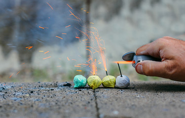 Man's hand lighting a series of smoke bombs