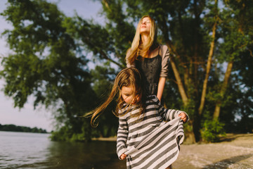 Mother and her little gaughter walking on a sandy river bank