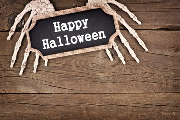Skeleton hands holding a Happy Halloween tag over an old rustic wood background