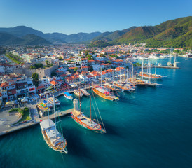 Wall Murals Port Aerial view of boats and beautiful architecture at sunset in Marmaris, Turkey. Colorful landscape with boats in marina bay, sea, city, mountains. Top view from drone of harbor with yacht and sailboat