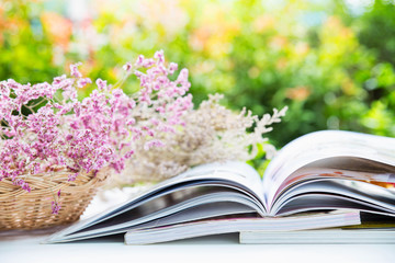 Open book  and there are dry flowers in rattan basket , colorful nature background and bokeh