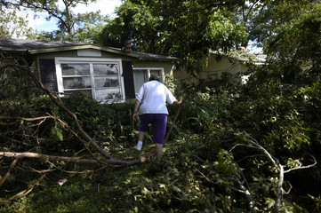 Carol Briggs, 70, walks over downed tree limbs while returning home for the first time after Hurricane Irma in Jacksonville