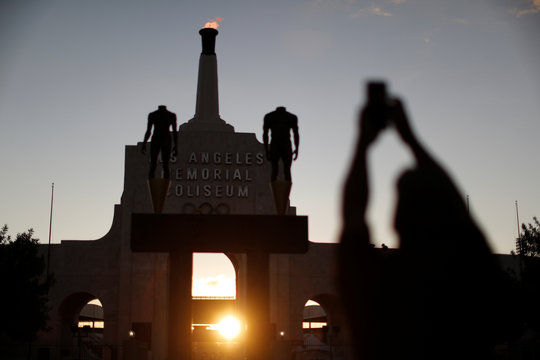 A man takes a photo at the Los Angeles Coliseum on the day Los Angeles was awarded the 2028 Olympic Games, in Los Angeles
