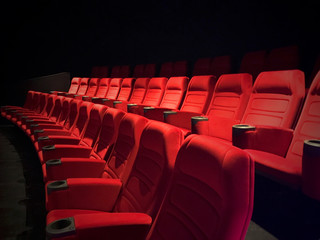 New unused movie theater seats. Red seat rows in auditorium.
