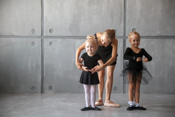 a young woman ballerina in a black dress, white pantyhose and pointe shoes teaches to dance the ballet of young girls ballerinas in black dresses and tights in a dark dance studio