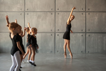 A young ballerina teaches to dance ballet of young girls ballerinas with black dresses, white pantyhose and pointe shoes in a dark dance studio