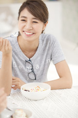 Woman holding spoon laughing