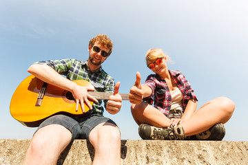 Young man hipster with guitar and woman.