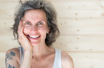 Head and shoulders view of natural looking middle aged woman with grey hair smiling with hand on face against pine board background (selective focus)