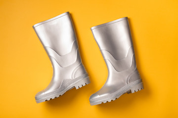 From above shot of trendy silver rain boots on orange background.