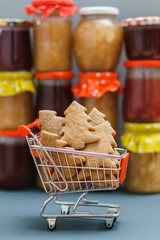 Christmas tree cookies in the shopping cart on the background with jam pots